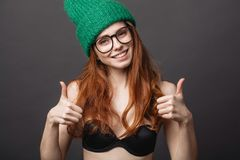 Redhead woman wearing black bra, glasses and green knit hat show two thumbs up royalty free stock image