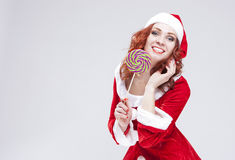 Portrait of Happy Smiling Santa Helper with Lollipop. Against white. Royalty Free Stock Photos