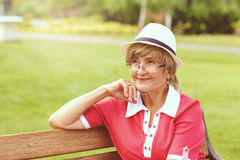Portrait of happy smiling senior woman. Sitting on a bench outside on sunny day Stock Image
