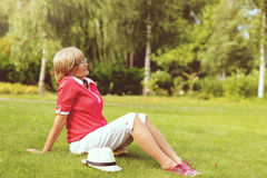 Portrait of happy smiling senior woman. Sitting on a grass outside on sunny day Stock Image