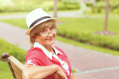 Portrait of happy smiling senior woman. Sitting on a grass outside on sunny day Royalty Free Stock Photos