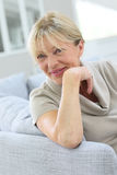 Portrait of happy smiling senior woman in sofa Stock Photo