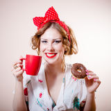 Portrait of happy smiling sexy blond girl beautiful young lady having fun holding red cup of beverage & donut. Picture of funny sexy blond pinup girl Stock Image