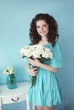 Portrait of happy smiling teen brunette with white roses bunch o. F flowers in blue dress posing ba the wall. Curly hairstyle Royalty Free Stock Images
