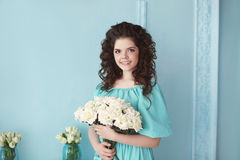 Portrait of happy smiling teen brunette with white roses bunch o. F flowers in blue dress posing ba the wall. Curly hairstyle Royalty Free Stock Photography
