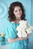 Portrait of happy smiling teen brunette with white roses bunch o. F flowers in blue dress posing ba the wall. Curly hairstyle Royalty Free Stock Image