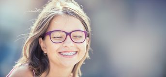 Portrait of a happy smiling teenage girl with dental braces and. Glasses stock photo