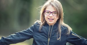 Portrait of a happy smiling teenage girl with dental braces and glasses royalty free stock photos