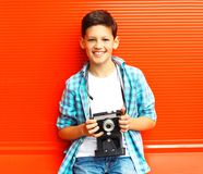 Portrait happy smiling teenager boy with retro camera on a red royalty free stock photo