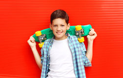 Portrait happy smiling teenager boy wearing a checkered shirtwith skateboard in city Stock Image