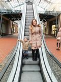 Portrait of happy smiling toddler boy with beautiful young mother on escalator at shopping mall royalty free stock photo