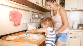 Portrait of happy smiling toddler boy with young mother baking and cooking on kitchen. Parent teaching and educating. Portrait of happy smiling toddler boy with royalty free stock photos