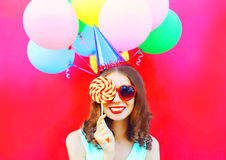 Portrait happy smiling woman in a birthday cap closes her eye with a lollipop on stick over an air colorful balloons on pink bac Stock Photo