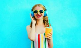 Portrait happy smiling woman holding cup of juice listening to music in wireless headphones on colorful blue. Background stock images