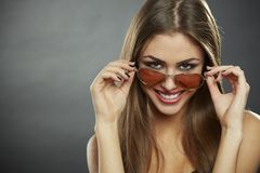 Woman looking over sunglasses and smiling Royalty Free Stock Images