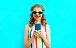 Portrait happy smiling woman holding phone listening to music in wireless headphones on colorful blue. Background stock images