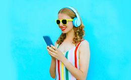 Portrait happy smiling woman holding phone listening to music in wireless headphones on colorful blue royalty free stock photo