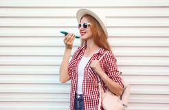 Portrait happy smiling woman holding phone using voice command recorder or calling, wearing summer round straw hat with bag stock photography