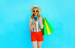 Portrait happy smiling woman holding smartphone with shopping bags in colorful t-shirt, summer straw hat, sunglasses stock images