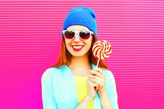 portrait happy smiling woman holds a lollipop on stick on pink Royalty Free Stock Photography
