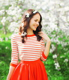 Portrait happy smiling woman with petals in her hair at spring flowers stock images