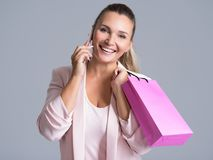 Portrait of happy smiling woman with pink bag that speaks on a m. Portrait of happy smiling woman with pink shopping bag that speaks on a mobile phone royalty free stock photography