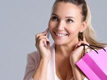 Portrait of happy smiling woman with pink bag that speaks on a m. Portrait of happy smiling woman with pink shopping bag that speaks on a mobile phone royalty free stock image