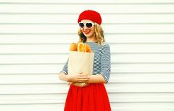 Portrait happy smiling woman wearing red beret holding paper bag with a long white bread baguette. On white wall background royalty free stock photos