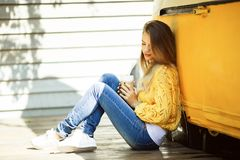 Pretty smiling woman is wearing yellow sweater drinking coffee latte near old retro bus. Portrait of happy smiling woman is wearing yellow knitted sweater and Royalty Free Stock Image