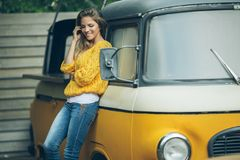 Happy smiling woman is wearing yellow sweater near old retro bus Stock Photography