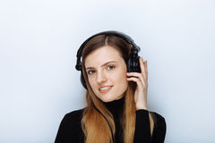 Portrait of happy smiling young beautiful woman in black sweater big dj headphones posing against white studio background Royalty Free Stock Photography