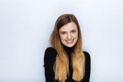 Portrait of happy smiling young beautiful woman in black sweater posing against white studio background Stock Images