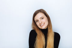 Portrait of happy smiling young beautiful woman in black sweater posing against white studio background Royalty Free Stock Photos