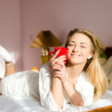 Portrait of happy smiling young blond pretty woman in bed with red cup in her hands & looking at camera Royalty Free Stock Photos