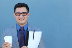 Portrait of happy smiling young business man with a suit, tie and classic glasses against blue background Stock Image