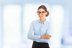 Portrait of happy smiling young cheerful businesswoman in glasses and blue clothing, with pen in crossed arms pose. Stock Photography
