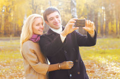 Portrait of happy smiling young couple together making selfie on smartphone Stock Photography