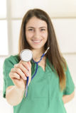 Portrait of happy smiling young female doctor listening Royalty Free Stock Photos