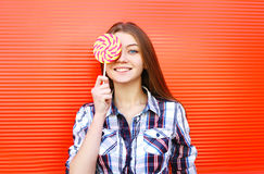Portrait happy smiling young girl with sweet caramel lollipop having fun Stock Photo