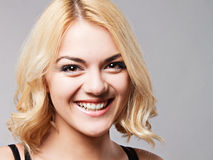 Portrait of the happy smiling young lady posing in studio. Royalty Free Stock Image
