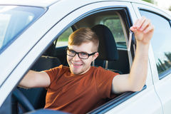 Portrait of happy smiling young man, buyer sitting in his new car and showing keys outside dealer office. Personal Stock Photography