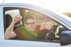 Portrait of happy smiling young man, buyer sitting in his new car and showing keys outside dealer office. Personal Royalty Free Stock Images