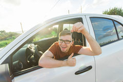 Portrait of happy smiling young man, buyer sitting in his new car and showing keys outside dealer office. Personal Royalty Free Stock Image