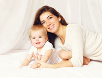Portrait of happy smiling young mother and cute baby on the bed Stock Photos