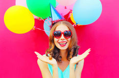 Portrait happy smiling young woman in a birthday cap is having fun over an air colorful balloons pink Royalty Free Stock Photography