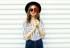 Portrait happy smiling young woman hiding her eye with red heart shaped lollipop in black round hat, white striped shirt on white. Wall background royalty free stock photography