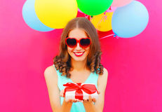 Portrait happy smiling young woman holds in hands a gift box over an air colorful balloons a pink background Royalty Free Stock Images