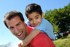 Portrait of happy son on the back of his father. Portrait of father and son having fun in the mountain Royalty Free Stock Photos