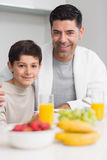 Portrait of happy son with father having breakfast Royalty Free Stock Photo