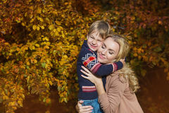 Portrait happy son strong hugs his mother in a park in the autumn. Portrait happy son strong hugs his mother in a park in autumn Stock Images